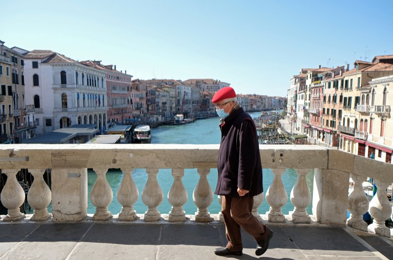A man wearing a protective mask on an empty Rialto Bridge on Sunday with an unprecedented lockdown across of all Italy imposed to slow the outbreak of coronavirus, in Venice, Italy, March 15, 2020. (Reuters Photo)