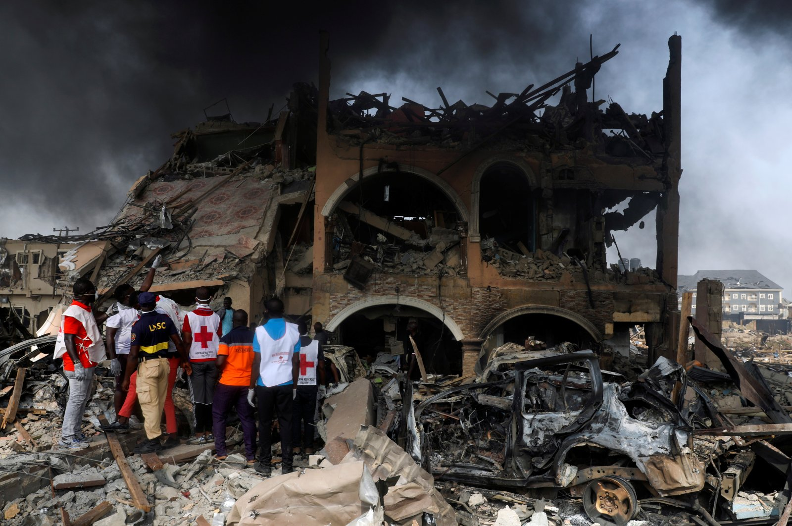 Paramedics and security men observe a building that was damaged by the pipeline explosion at Abule Ado in Lagos, Nigeria, March 15, 2020. (Reuters Photo)