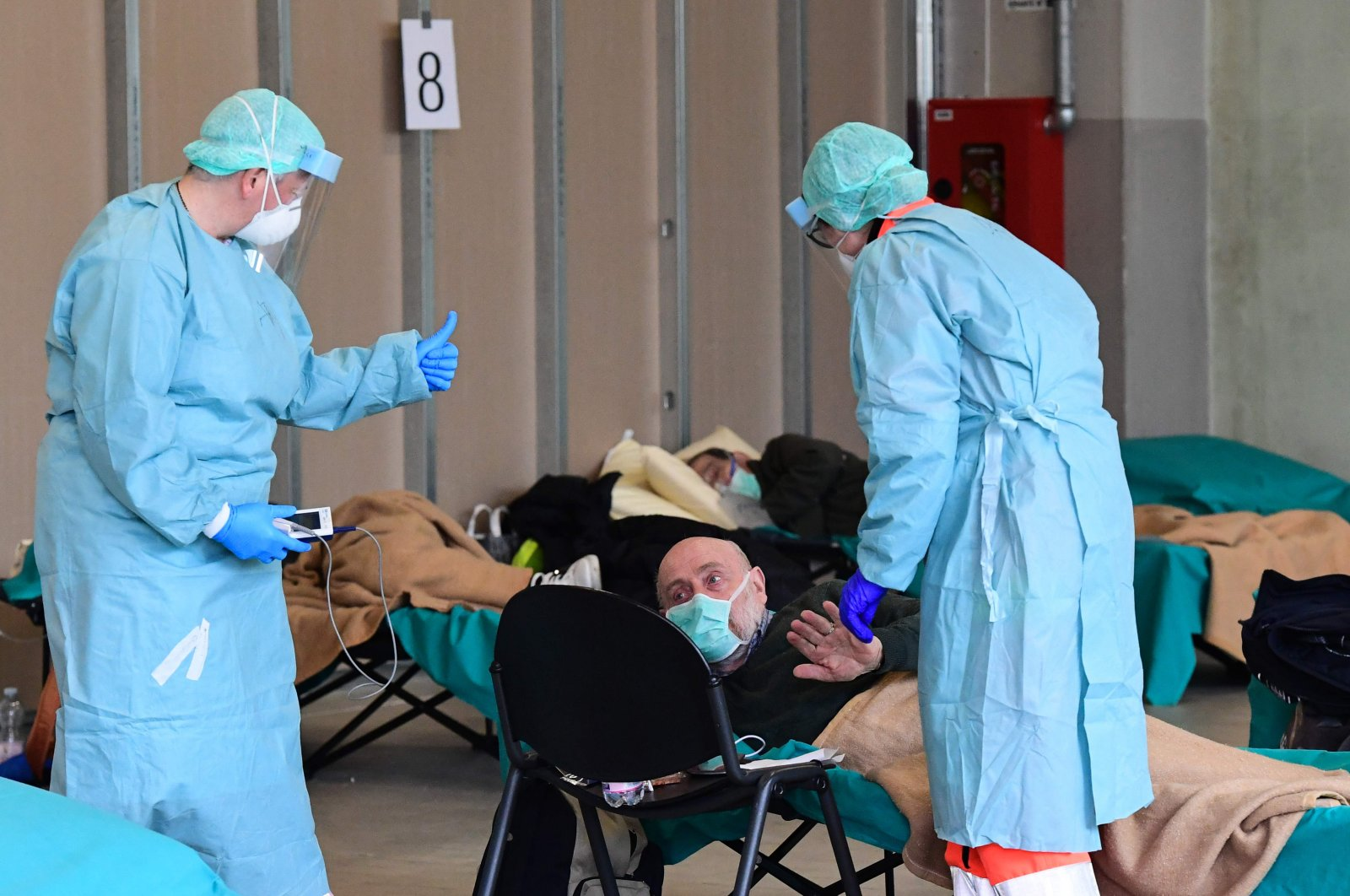 Hospital employees wearing protection masks and gear tend to a patient at a temporary emergency structure set up outside the accident and emergency department, where any new arrivals presenting symptoms of COVID-19 are being tested, at the Brescia hospital, Lombardy,, March 13, 2020. (AFP Photo)