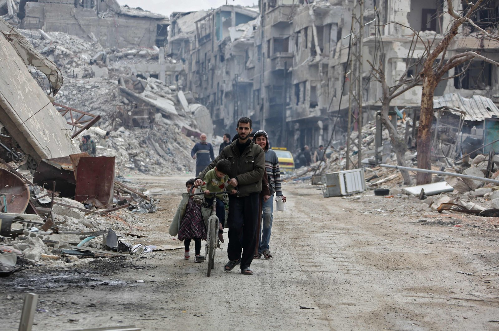 In this file photo taken on March 30, 2018, civilians walk in a destroyed neighborhood in the former opposition-held town of Harasta in eastern Ghouta, a week after regime forces retook the town from the opposition. (AFP Photo)