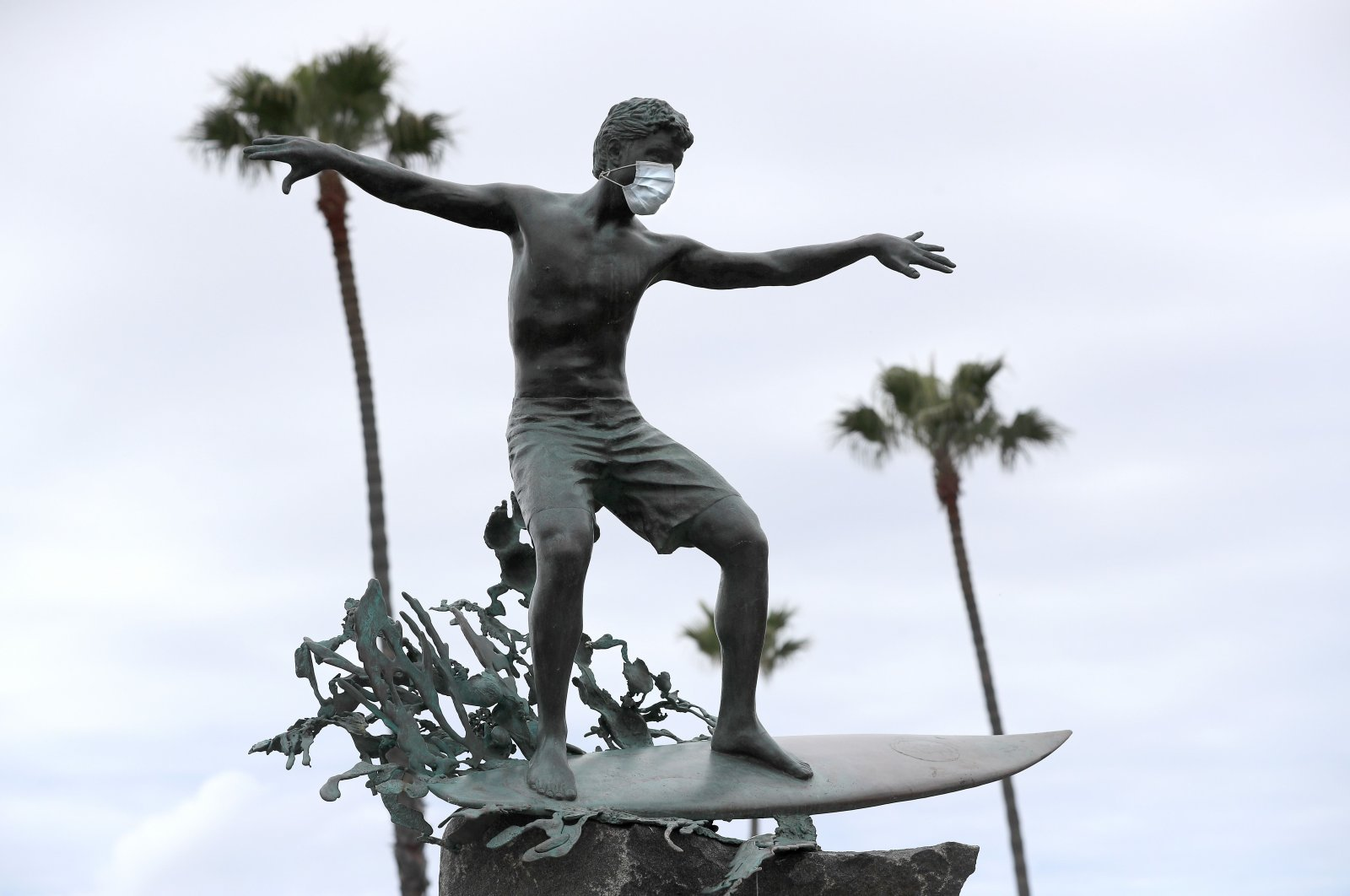 """The """"Magic Carpet Ride"""" statue along Highway 101 had a surgical mask put on it, Cardiff-by-the-Sea, California, March 15, 2020. (AFP Photo)"""