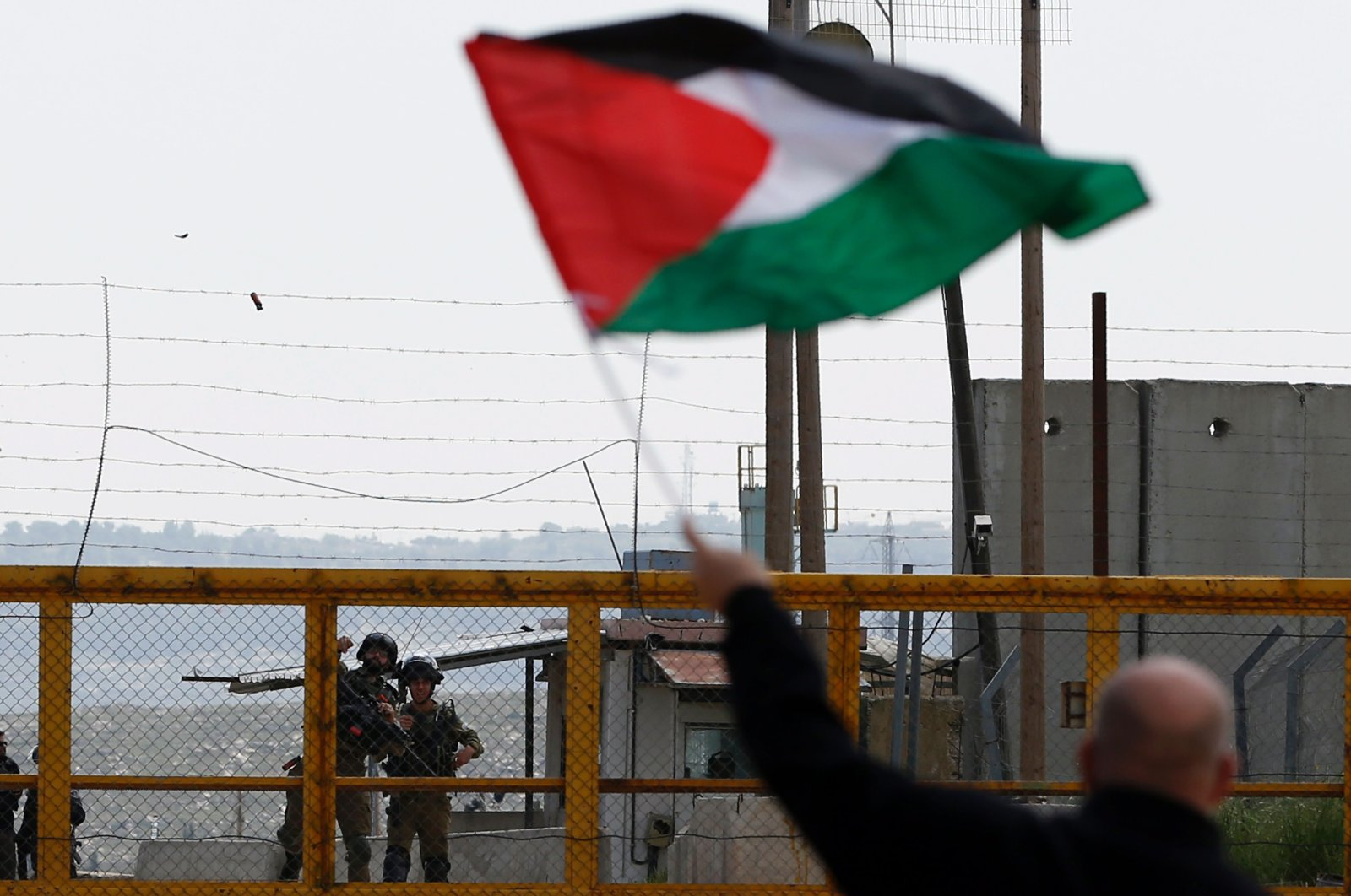 A Palestinian protester waves his national flag in front of Israeli security forces outside the compound of the Israeli-run Ofer prison near Betunia in the Israeli-occupied West Bank, March 30, 2016. (AFP Photo)
