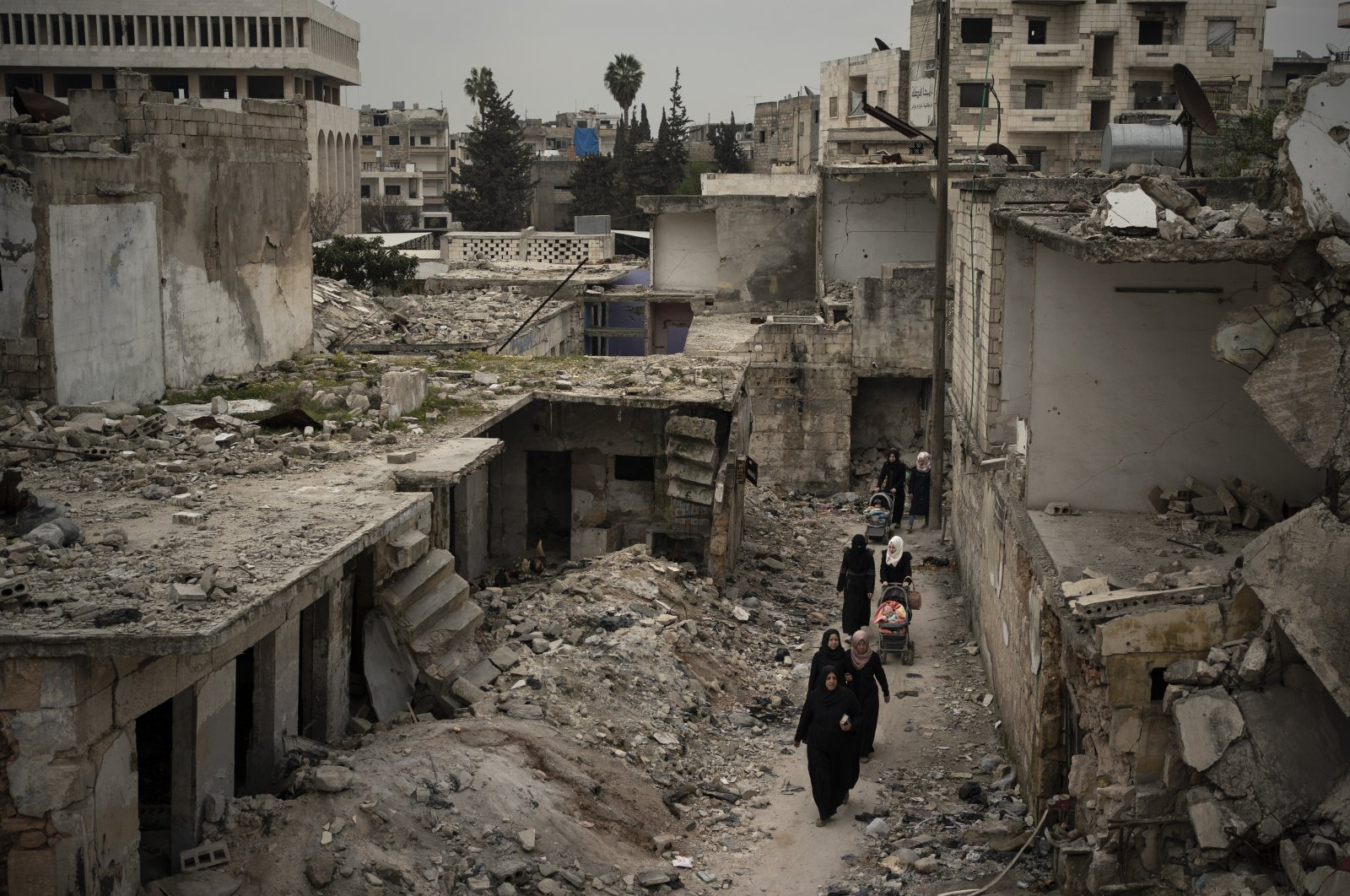 Women walk in a neighborhood heavily damaged by airstrikes in Idlib, Syria, Thursday, March 12, 2020. (AP)