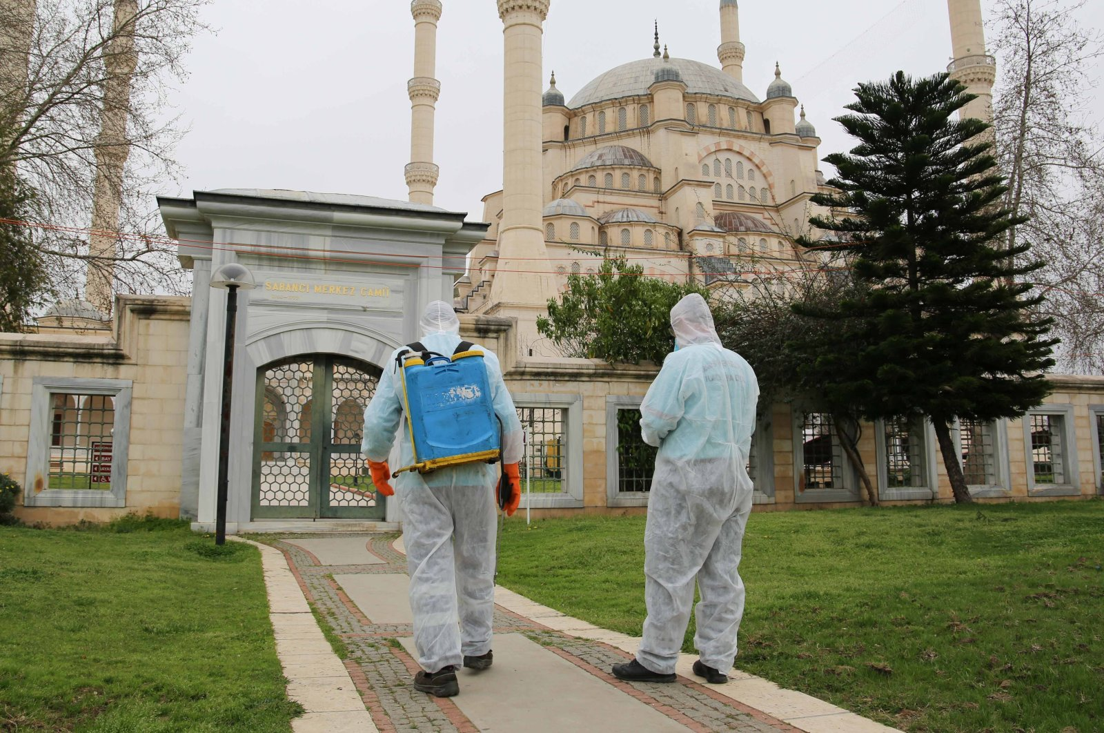 Men wearing protective suits spray disinfectant at a mosque amid the spread of the coronavirus (COVID-19) in Adana, March 12, 2020. (Photo by İHA)