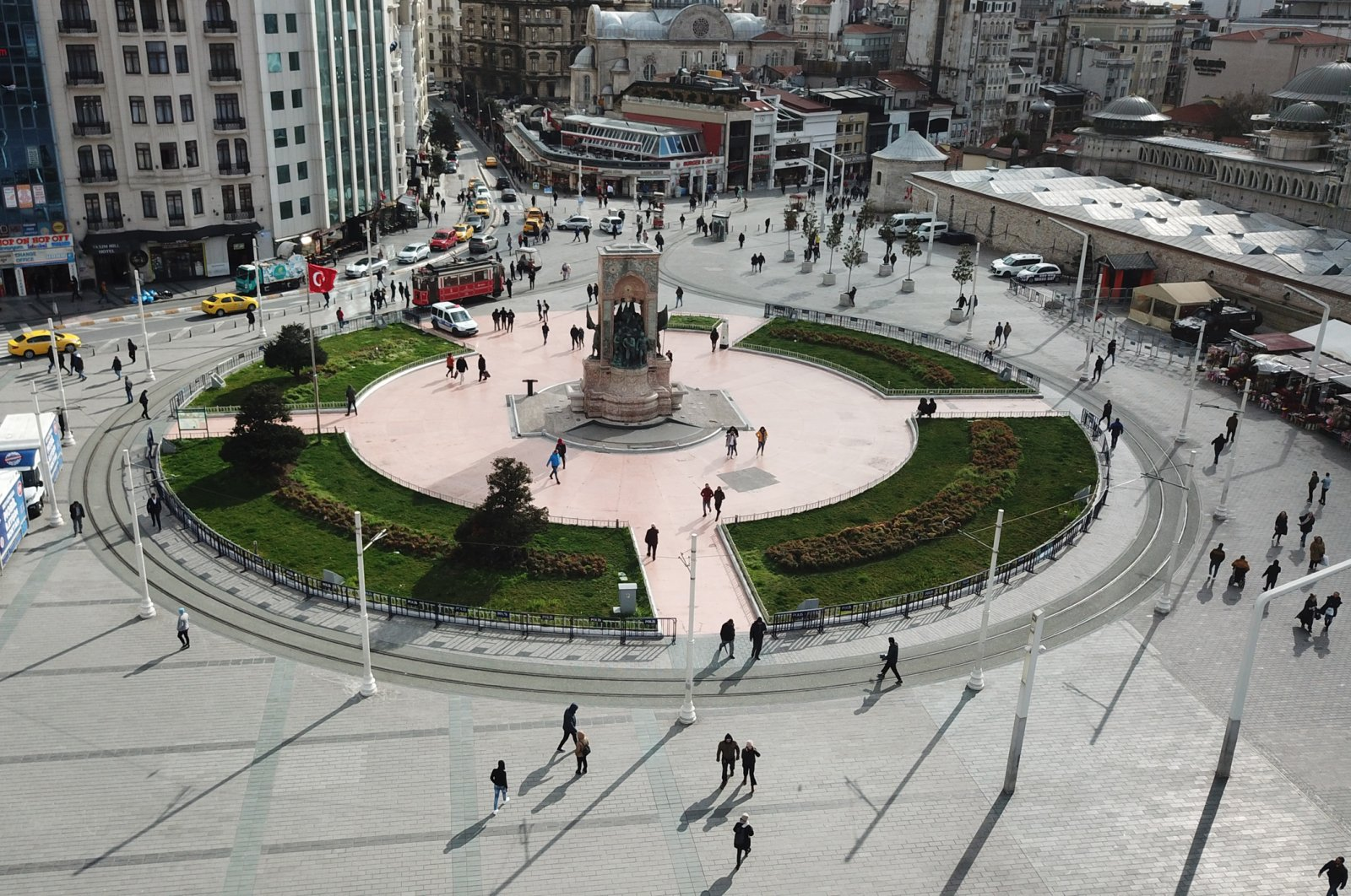 People walk at Taksim Square, Monday, March 16, 2020, Istanbul. The square was one of the busiest places in the city before the virus scare emerged. (DHA Photo)