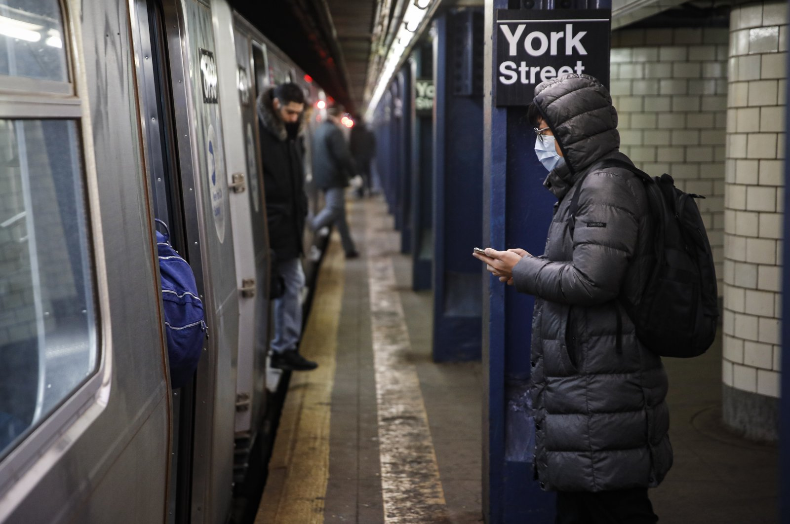 A subway user wearing a face mask waits to board a car in the Brooklyn borough of New York, Monday, March 16, 2020. (AP Photo)