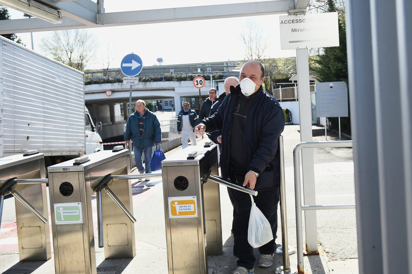 Fiat Chrysler Automobiles worker, wearing a protective face mask, leaves a Mirafiori plant, Turin, Italy, Tuesday, March 10, 2020. (Reuters Photo)
