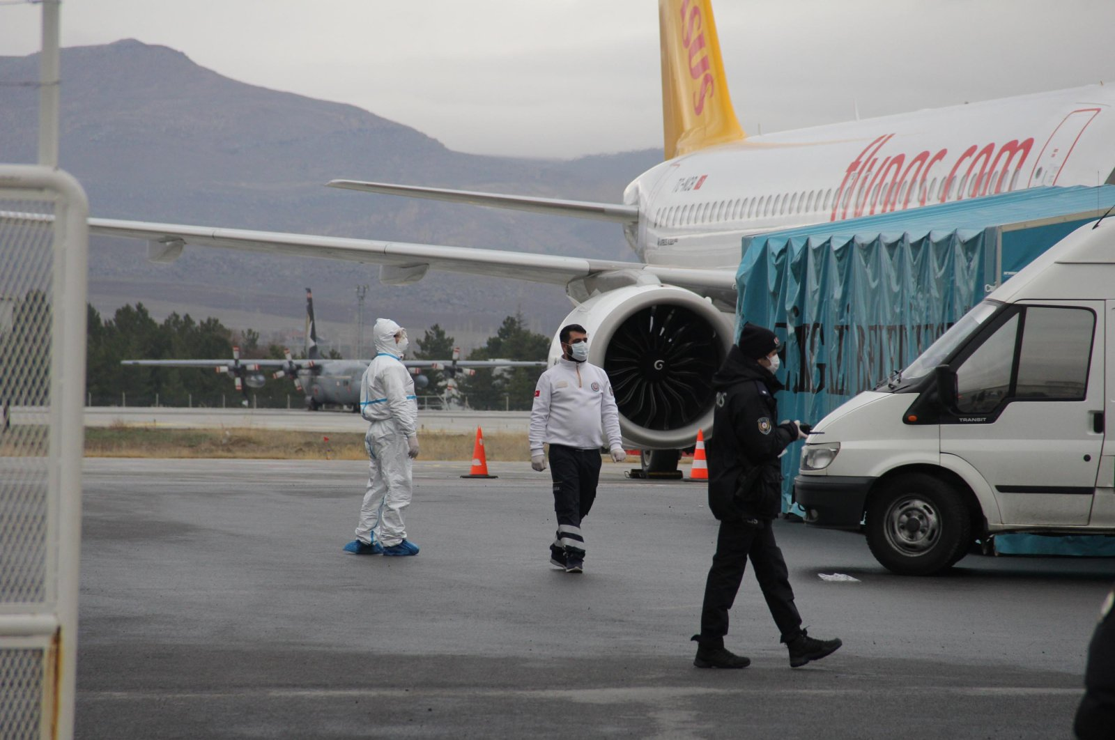 A health worker in protective suit stands near a parked Pegasus Airlines plane in Kayseri, Turkey, March 16, 2020. (DHA Photo)