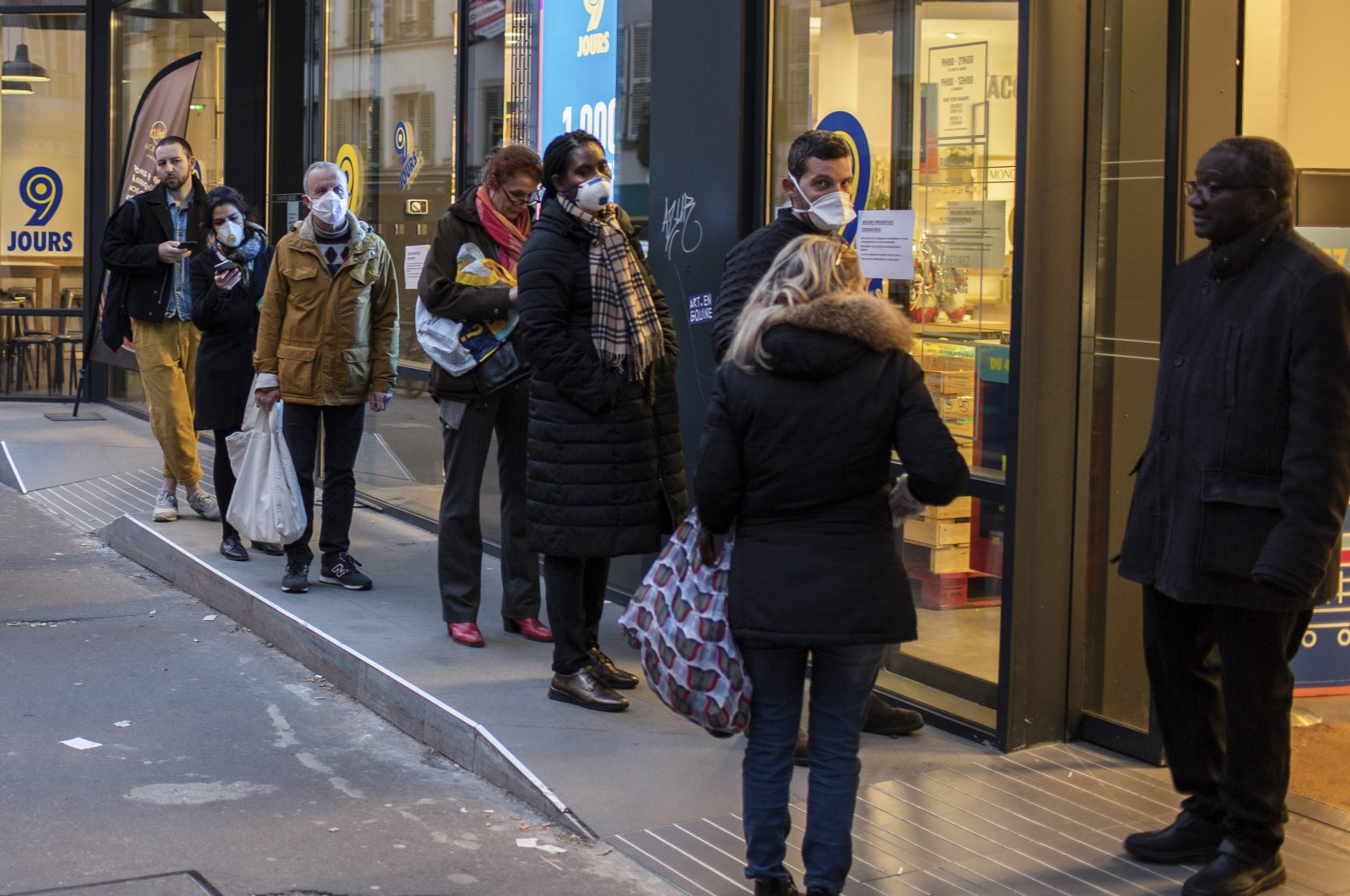 People wearing protective masks line up using social distancing to queue at a supermarket in Paris, Monday, March 16, 2020. (AP Photo)