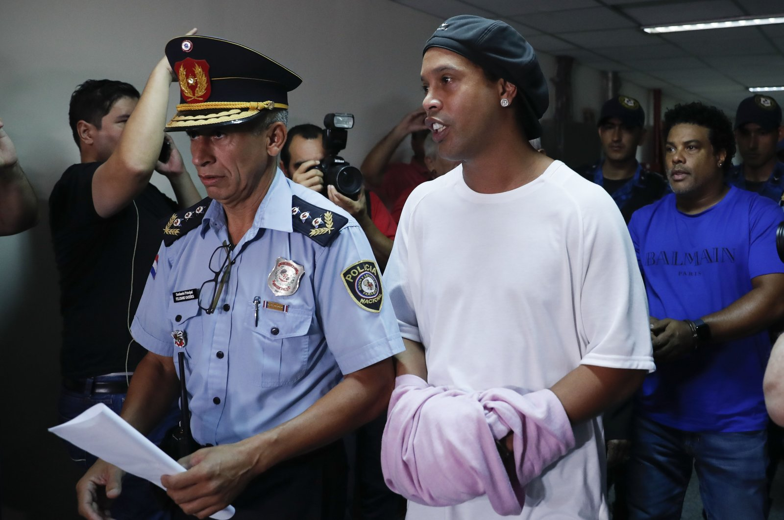 Former football star Ronaldinho is escorted by police officers to declare to judge Clara Ruiz Diaz at Justice Palace in Asuncion, Paraguay, Saturday, March 7, 2020. (AP Photo)