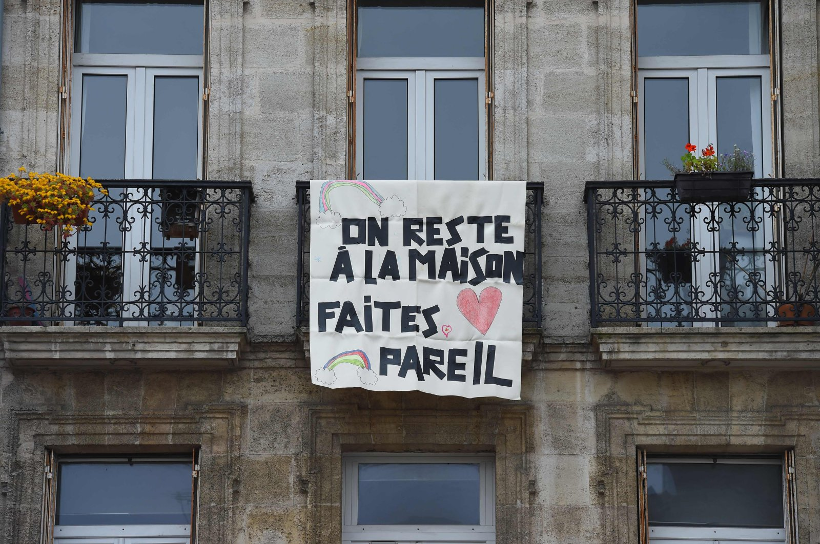 """A sign hanging from a balcony reads """"We stay at home, do the same,"""" Bordeaux, France, Monday, March 16, 2020. (AFP Photo)"""