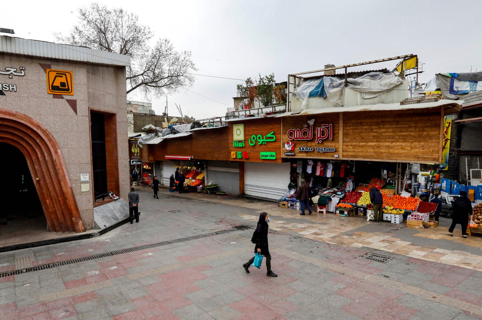 A woman wearing a protective face mask walks past Tajrish bazaar in Iran's capital Tehran on March 14, 2020. (AFP Photo)