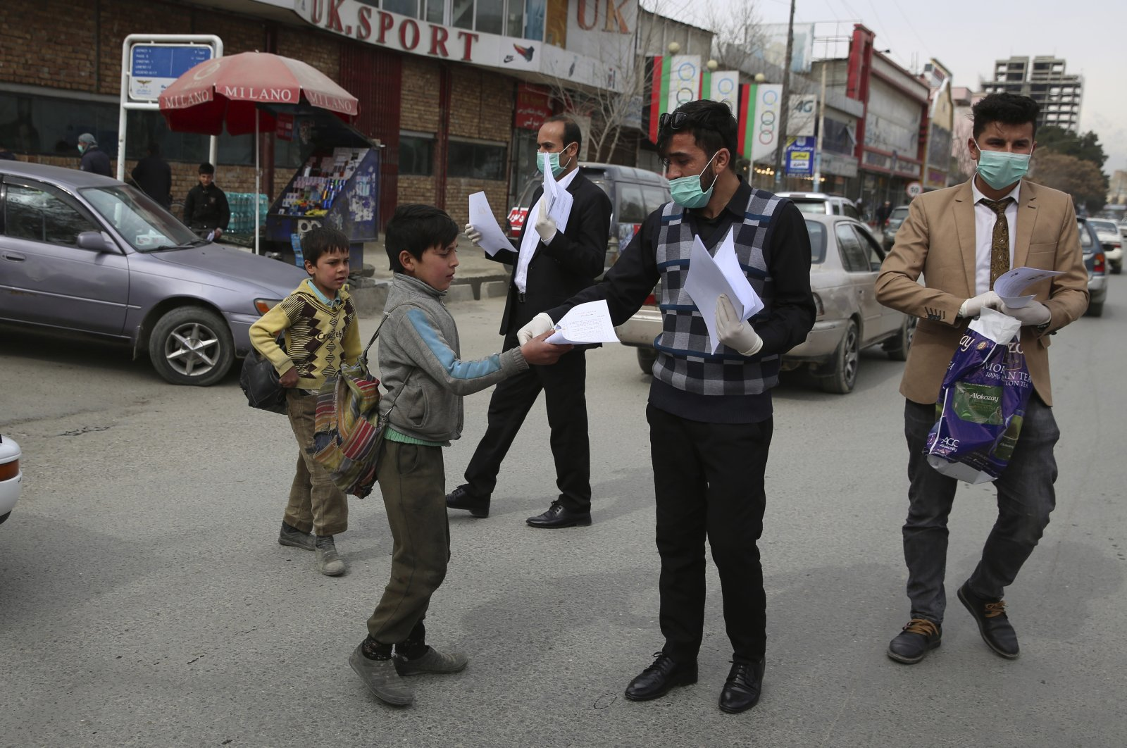Civil society activists wearing face masks distribute written information to passersby, Kabul, Monday, March 16, 2020. (AP Photo)