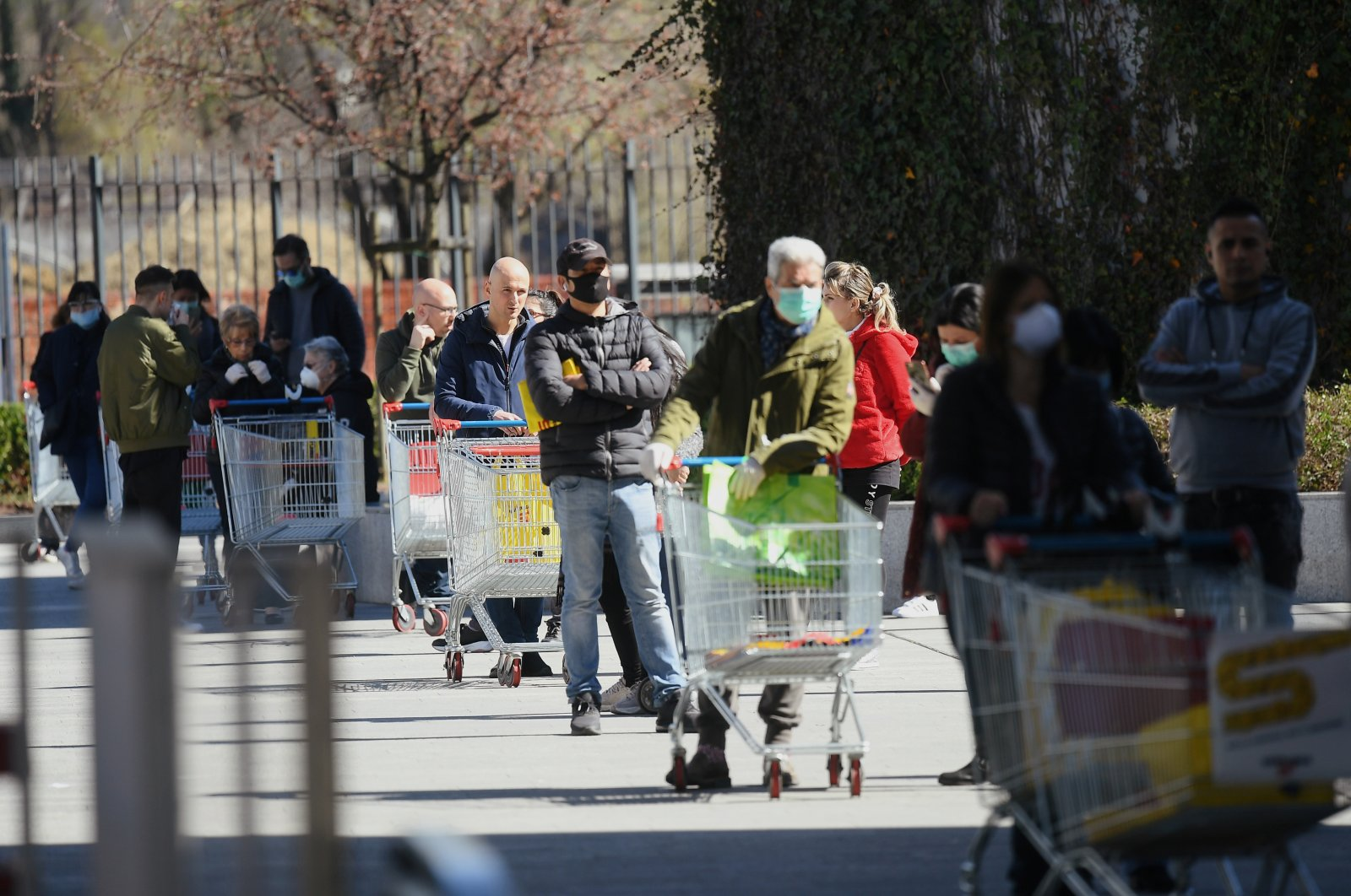 People wait in front of a supermarket on the second day of the lockdown across the country imposed to slow the outbreak of the novel coronavirus, Milan, Italy, Wednesday, March 11, 2020. (Reuters Photo)