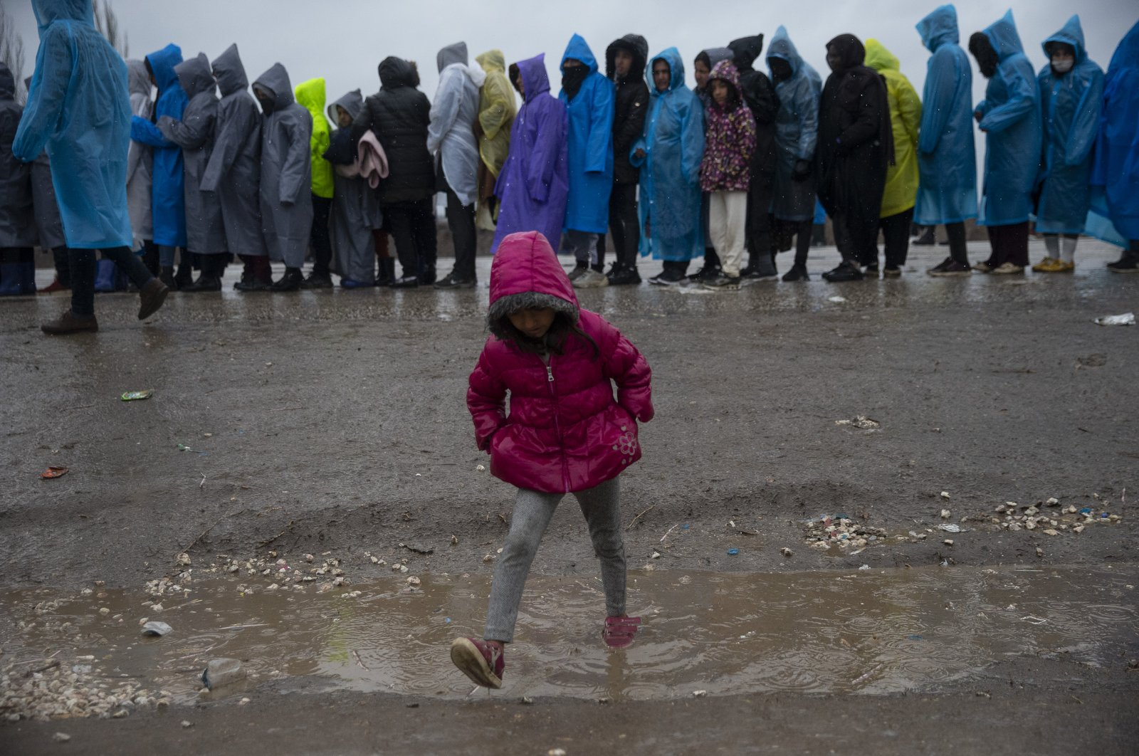 A child walks in the mud as asylum-seekers continue to wait at the Turkish-Greek border despite harsh weather conditions, March 15, 2020 (AA Photo)