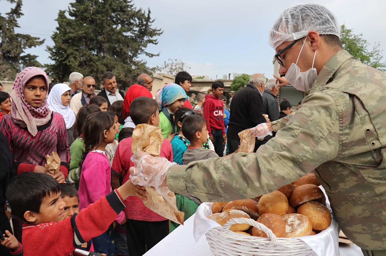 A Turkish soldier distributes bread to Afrin locals after Operation Olive Branch. (AA)
