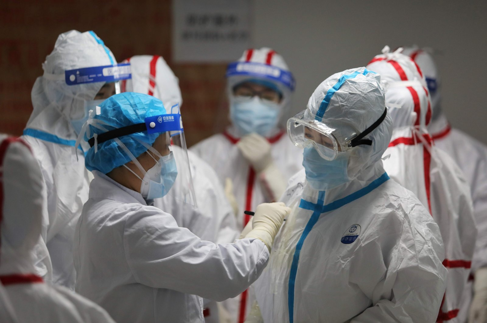 Medical staff write messages on their protective suits before attending to COVID-19 coronavirus patients at the Red Cross Hospital, Wuhan, March 16, 2020. (AFP Photo)