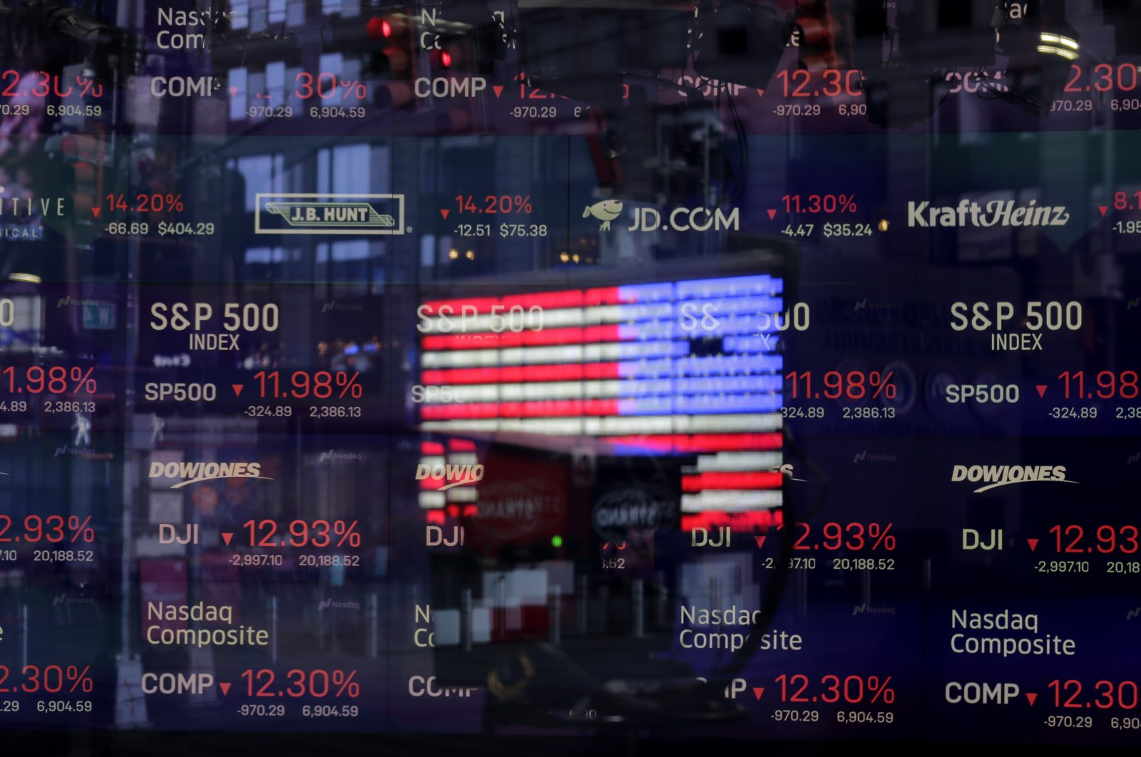 A United States flag is reflected in the window of the Nasdaq studio, which displays indices and stocks down, in Times Square, New York, Monday, March 16, 2020. (AP Photo)