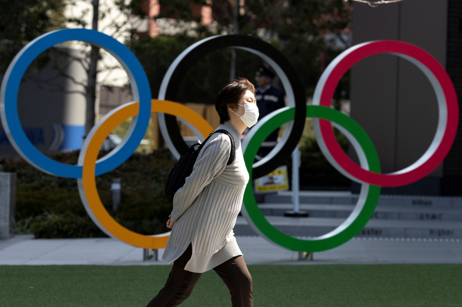 A woman wearing a protective face mask amid the coronavirus outbreak walks past the Olympic rings in front of the Japan Olympics Museum in Tokyo, Japan, March 13, 2020. (Reuters Photo)