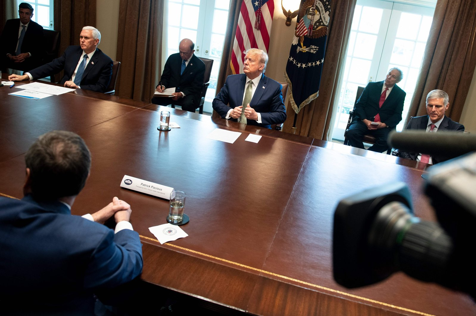 U.S. President Donald Trump and U.S. Vice President Mike Pence listen during a meeting with hotel and tourism executives in the Cabinet Room of the White House about the effect of the novel coronavirus epidemic, Tuesday, March 17, 2020. (AFP Photo)