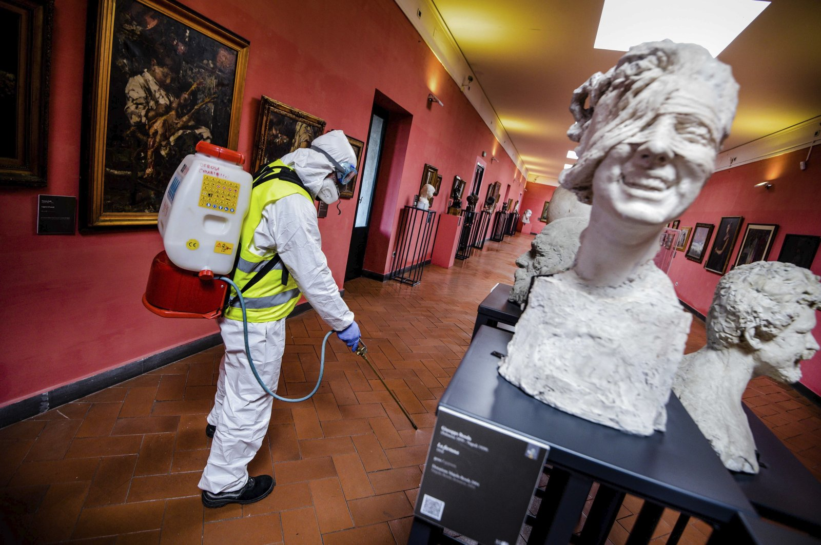 A worker sprays disinfectant to sanitize against coronavirus in the museum hosted by the Maschio Angioino medieval castle, in Naples, Italy, Tuesday, March 10, 2020. (LaPresse via AP)