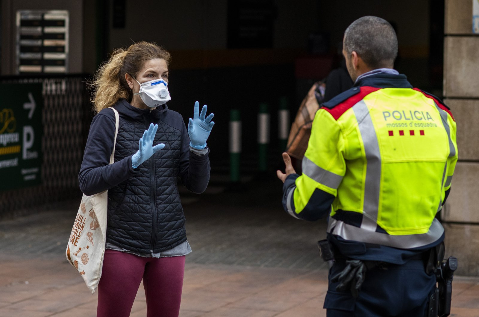 A woman wearing a face mask and gloves speaks with a Catalan police officer in Barcelona, Spain, Wednesday, March 18, 2020. (AP Photo)