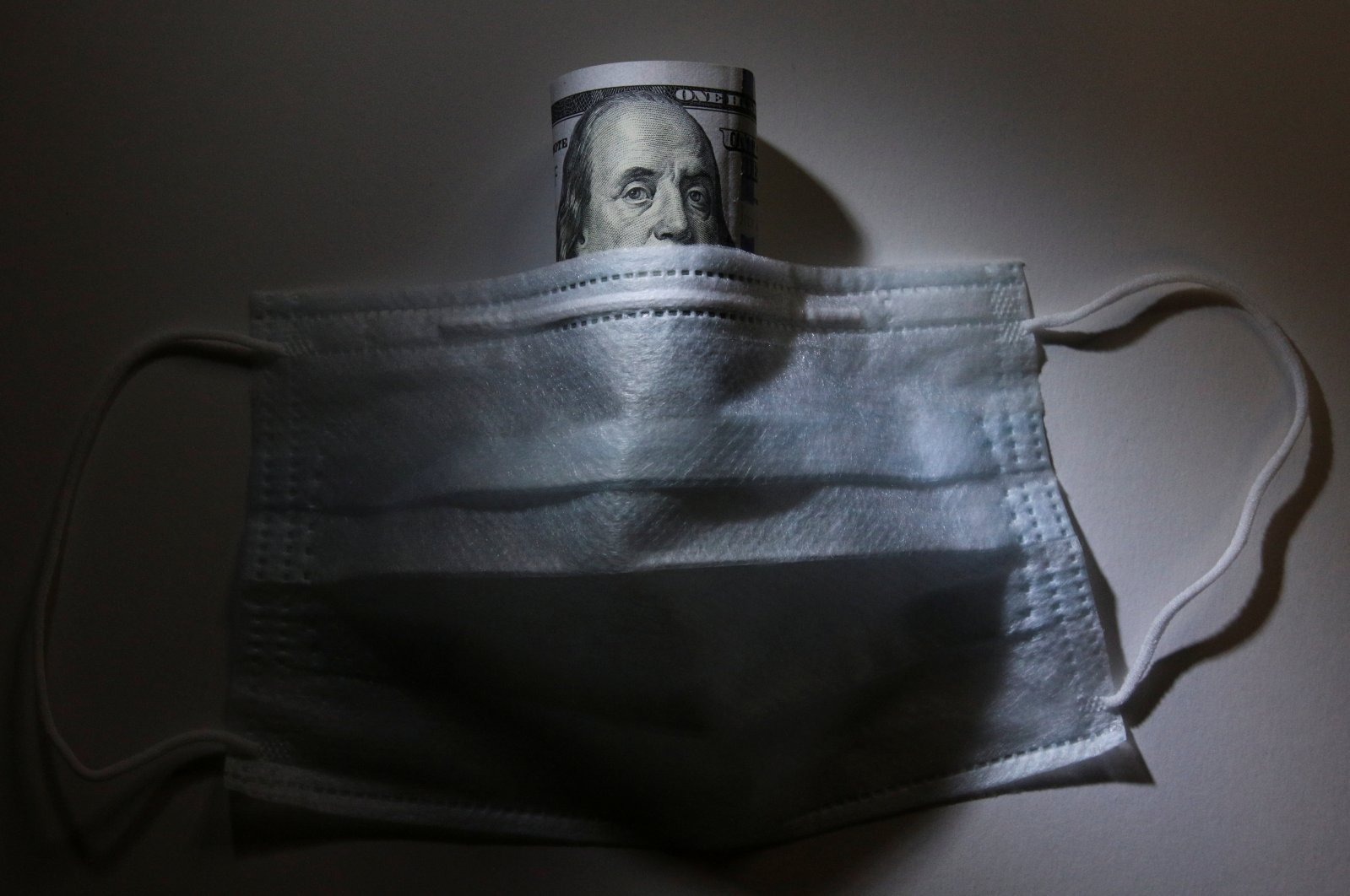 A U.S. dollar banknote is pictured behind a protective mask, a widely used preventive measure against the coronavirus, in this illustration taken Tuesday, March 17, 2020. (Reuters Photo)