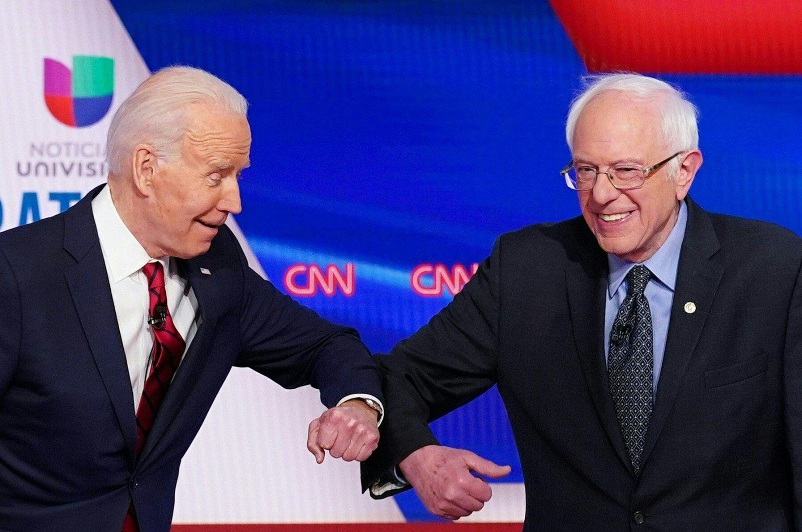 Democratic presidential hopefuls former U.S. Vice President Joe Biden (L) and Sen. Bernie Sanders (R) greet each other with an elbow bump, Washington, D.C., March 15, 2020. (AFP Photo)
