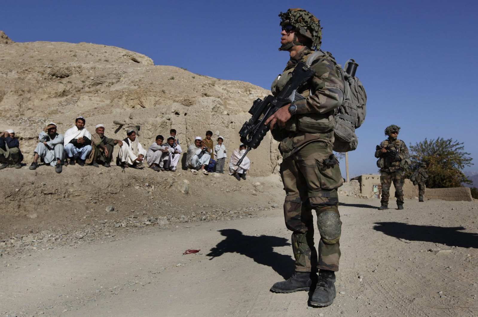 NATO soldiers patrol as Afghan men look on during an operation in the Tagab Valley, Nov. 15, 2009. (AP Photo)