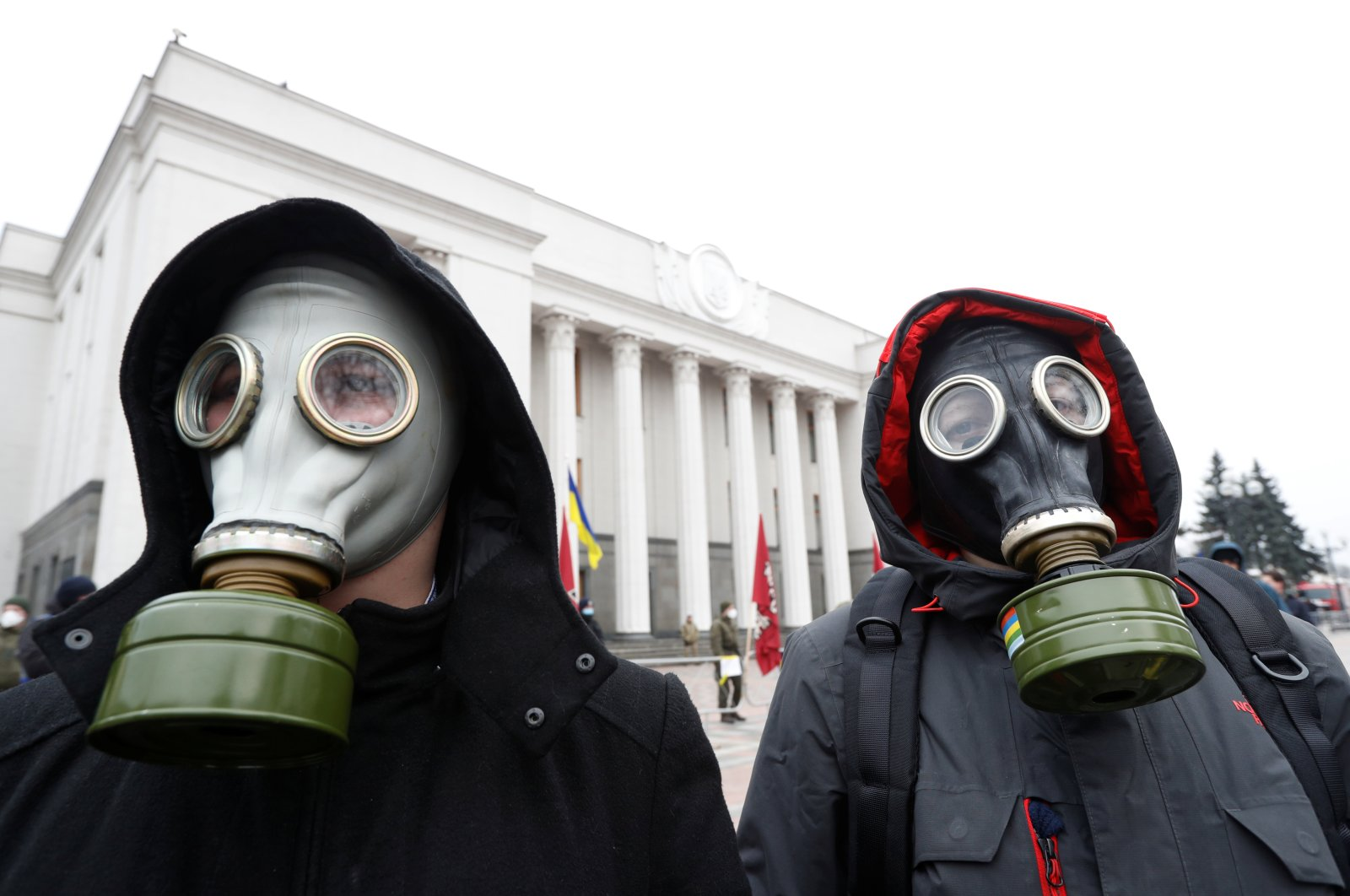 Activists wearing gas masks take part in a rally demanding to quarantine lawmakers amid coronavirus concerns, in front of the Ukrainian parliament building in Kiev, Ukraine March 17, 2020.  (REUTERS Photo)