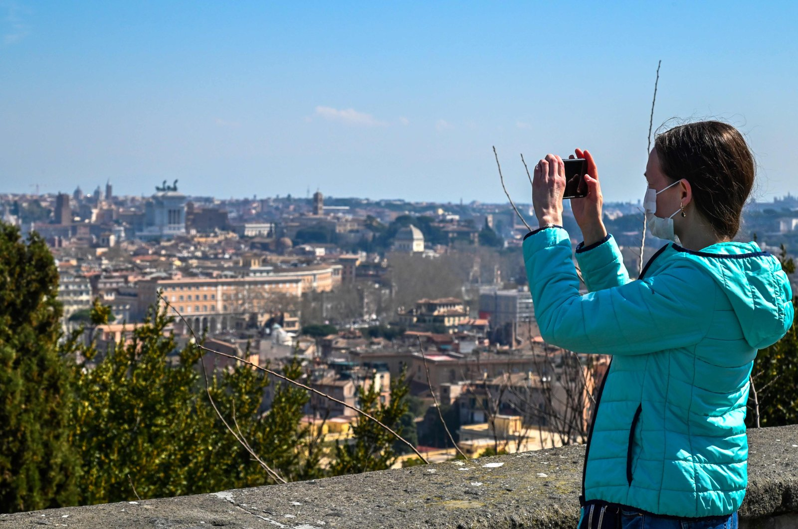 A woman wearing a face mask takes a photo of Rome from the Gianicolo terrace on March 18, during the country's lockdown within the new coronavirus crisis. (AFP Photo)