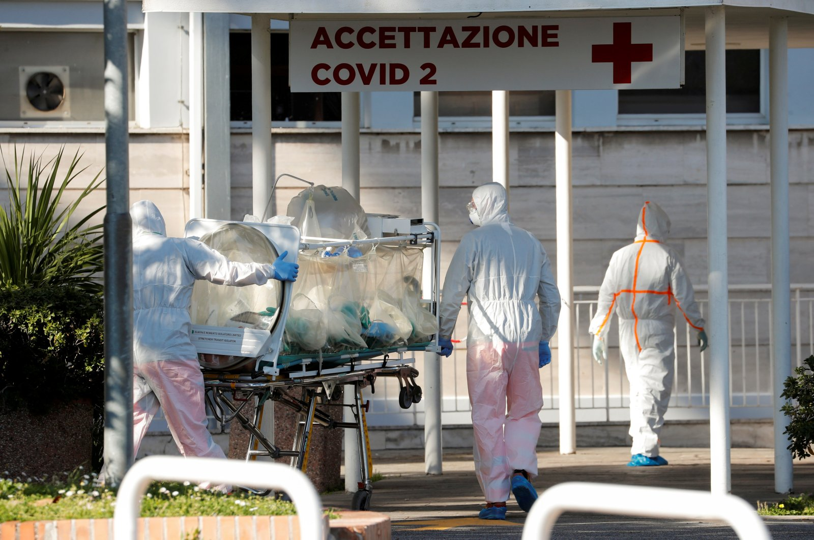 Medical workers in protective suits push an isolation stretcher in front of the Columbus Clinic, where patients suffering from coronavirus disease (COVID-19) were moved from Spallanzani Hospital, in Rome, March 16, 2020. (Reuters Photo)