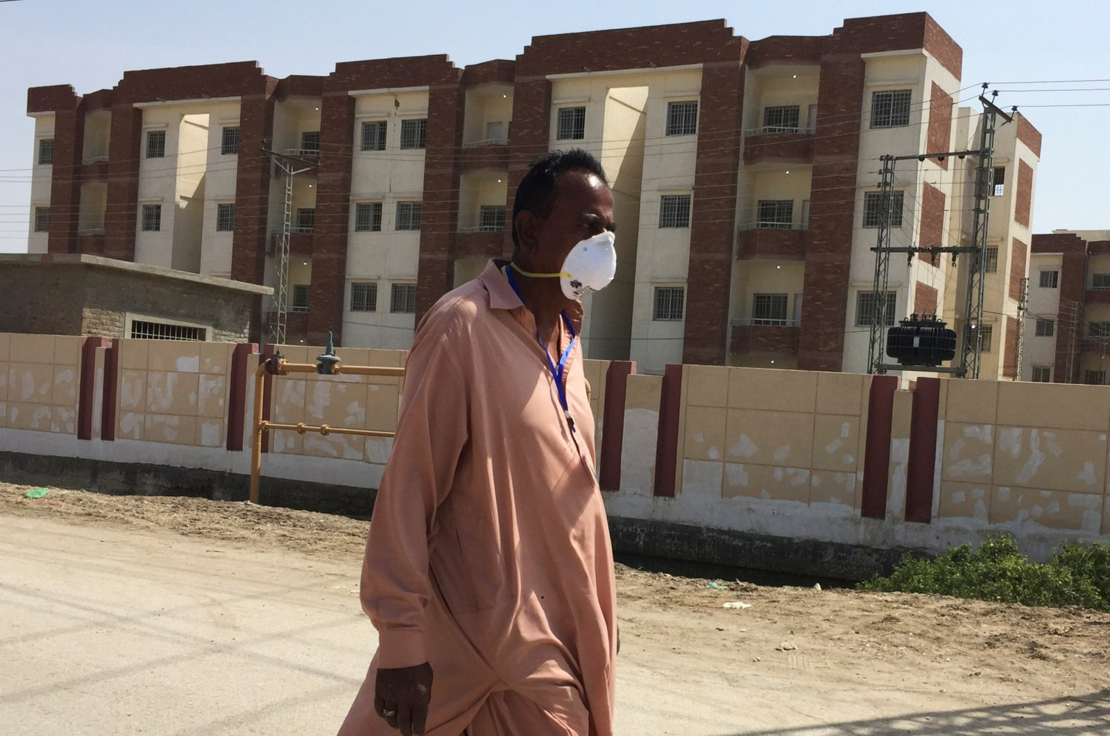 A man wears a protective mask following an outbreak of the coronavirus disease (COVID-19), as he walks in front of buildings, declared by the government as quarantine for the suspected pilgrims, who crossed Taftan border post with Iran, in Sukkur, Pakistan March 18. (Reuters Photo)