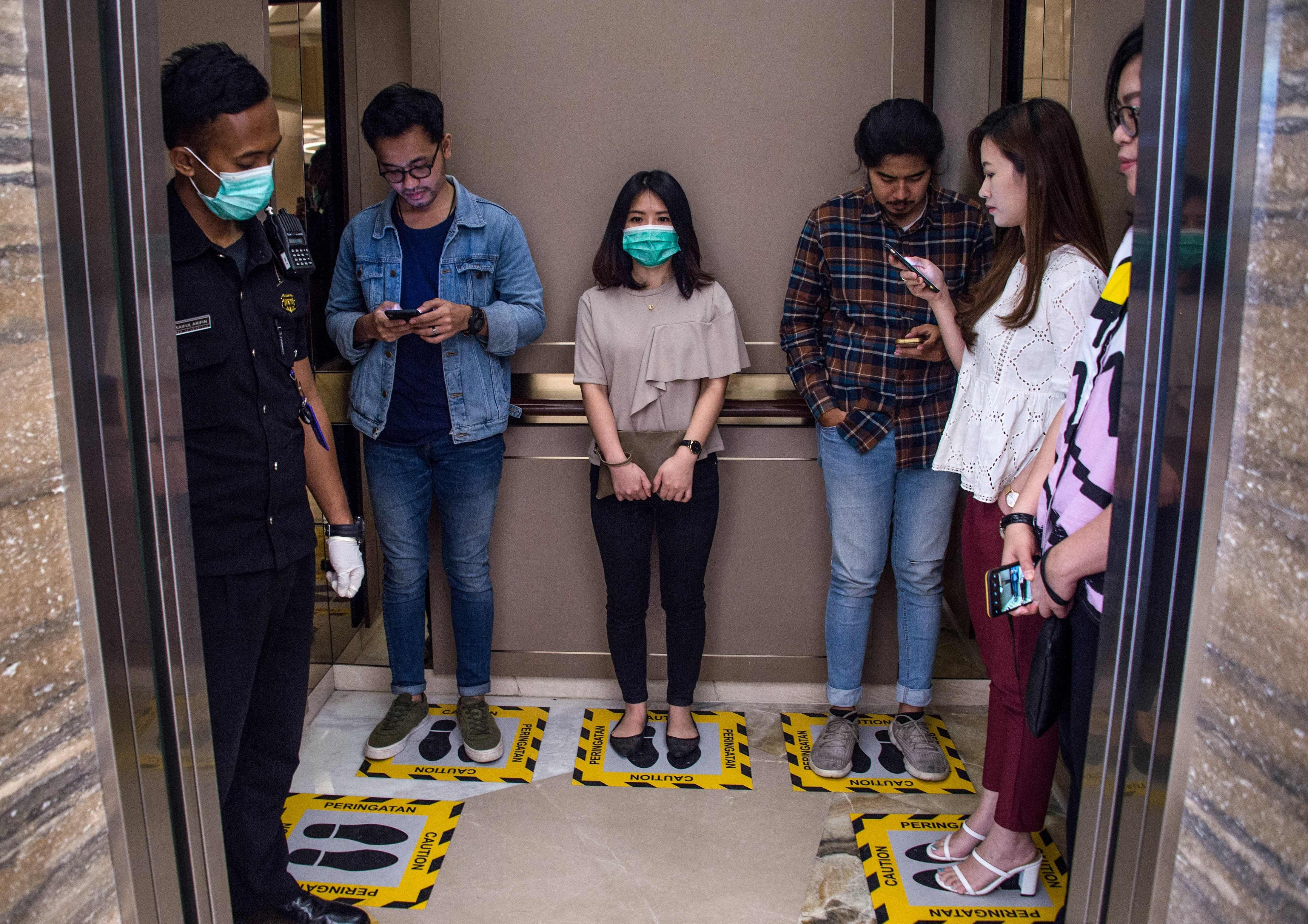 People stand on designated areas to ensure social distancing inside an elevator at a shopping mall in Surabaya on March 19, 2020, amid concerns of the COVID-19 coronavirus outbreak. (AFP Photo)