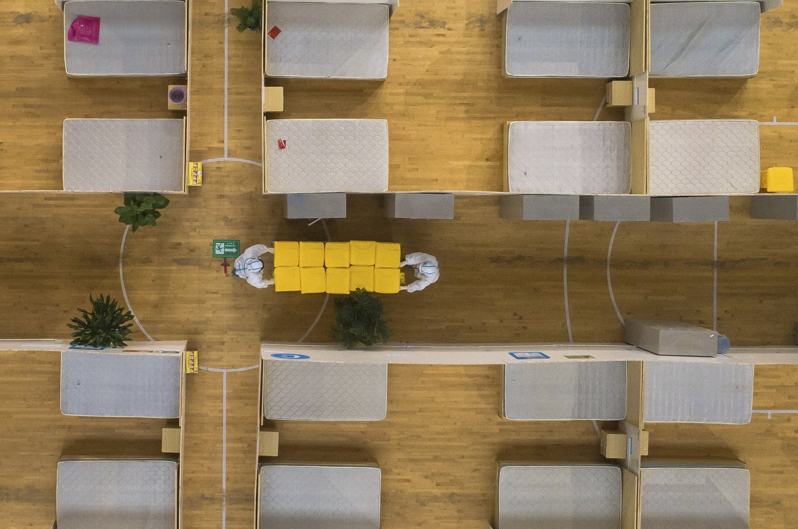 In this March 8, 2020, photo released by Xinhua News Agency, an aerial view shows staff members clean up an empty makeshift hospital in Wuhan, central China's Hubei Province. (Xinhua via AP)