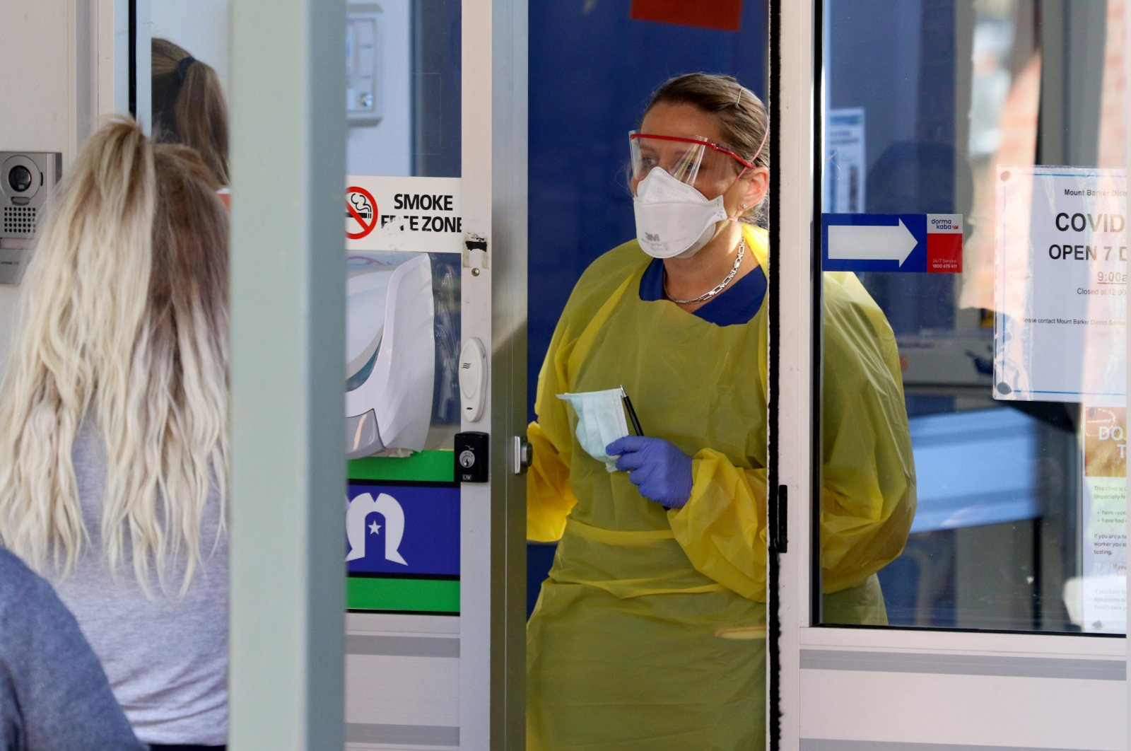 A nurse speaks with patients at the door of a new coronavirus disease (COVID-19) clinic opening at Mount Barker Hospital in Adelaide, Australia, March 17, 2020.  (AAP Image via Reuters)