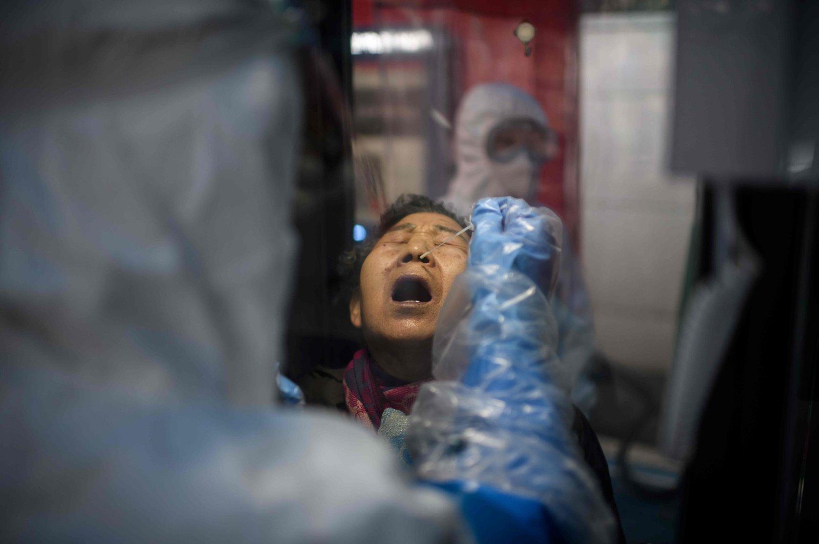 A woman receives a COVID-19 novel coronavirus test swab at a testing booth outside the Yangji hospital in Seoul, South Korea, March 17, 2020. (AFP Photo)