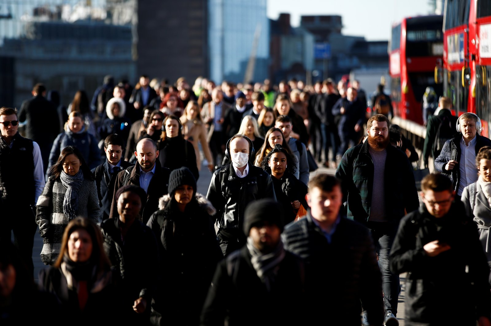 People, some wearing protective face masks, walk over London Bridge, London, Britain, Monday, March 16, 2020. (Reuters Photo)