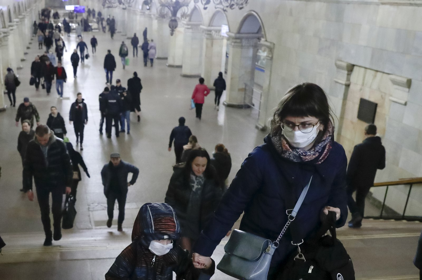 A woman with her child wear medical masks walk inside the Komsomolskaya Metro station, Moscow, March 18, 2020. (AP Photo)