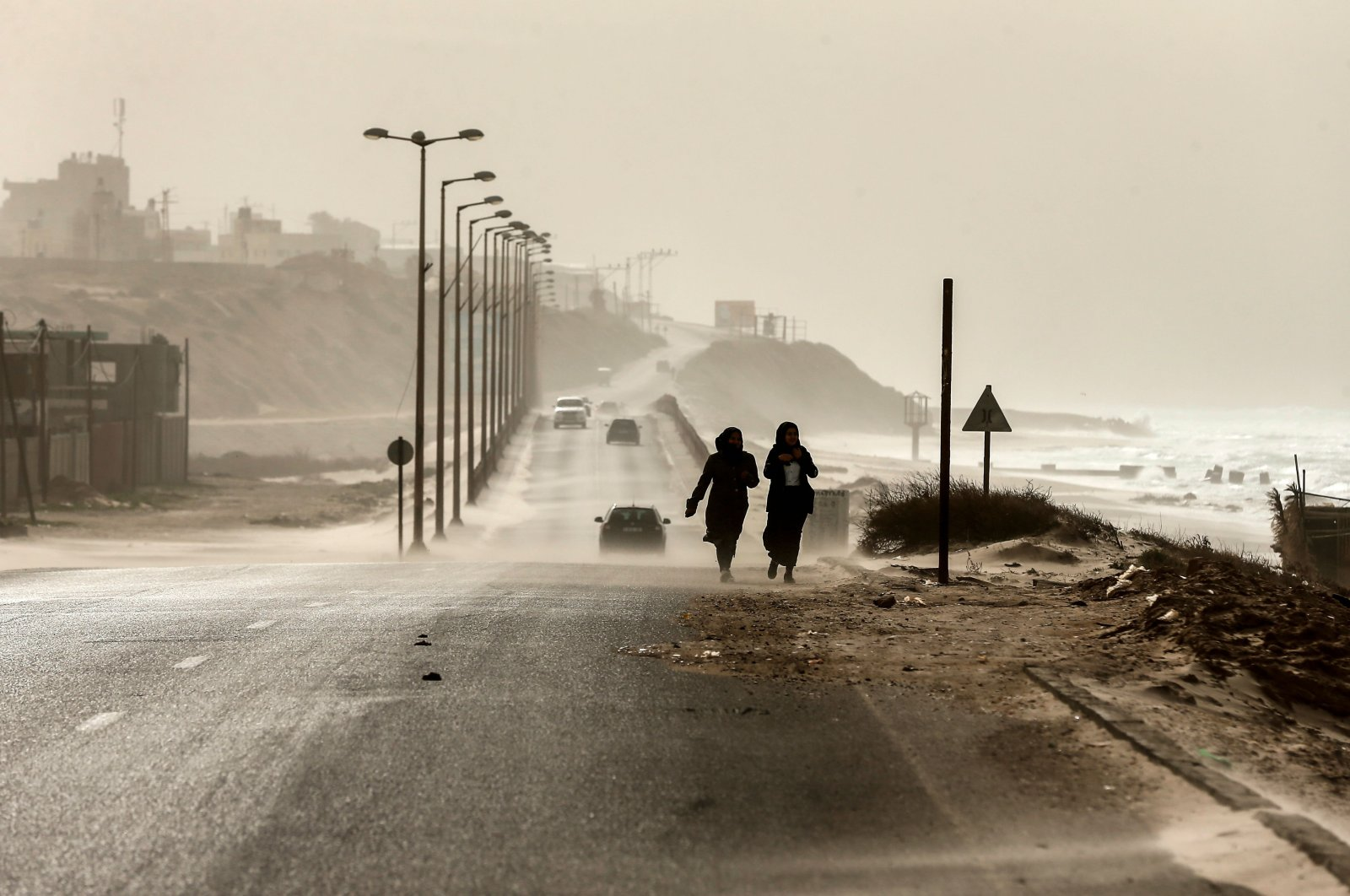 Two women walk along the sea front as heavy winds blow dust and sand across a main road in occupied Gaza City, Jan. 6, 2019. (AFP Photo)