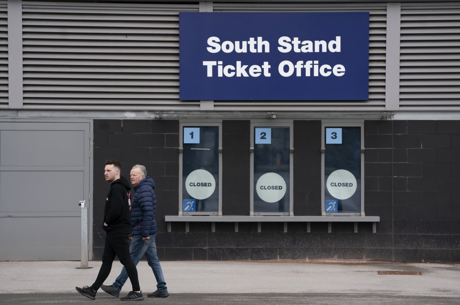 Men walk by a closed ticket office at the Etihad Stadium where Manchester City were due to play Burnley in an English Premier League soccer match, in Manchester, England, Saturday March 14, 2020. (AP Photo)