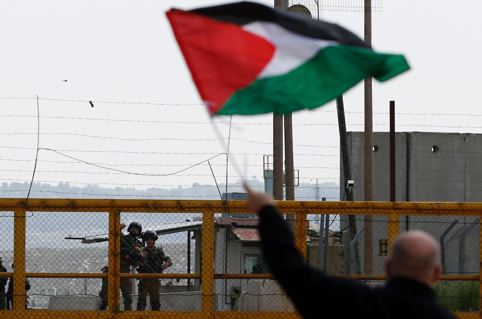 A Palestinian protester waves his national flag in front of Israeli security forces outside the compound of the Israeli-run Ofer prison near Betunia in the Israeli occupied West Bank, March 30, 2016. (AFP Photo)