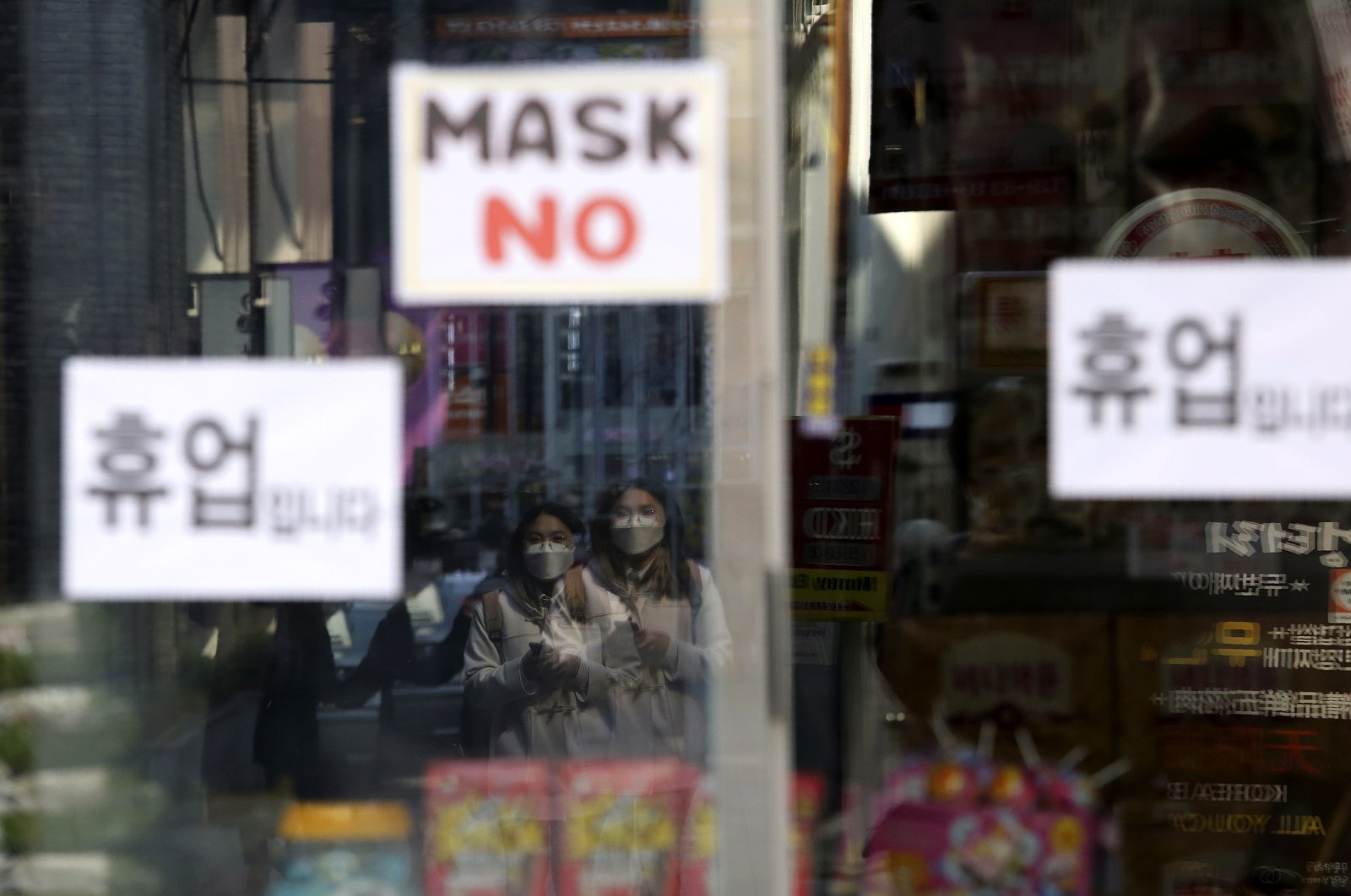 Women wearing a face mask are reflected on a window of a temporarily closed store in Seoul, South Korea, Wednesday, March 18, 2020. (AP Photo)