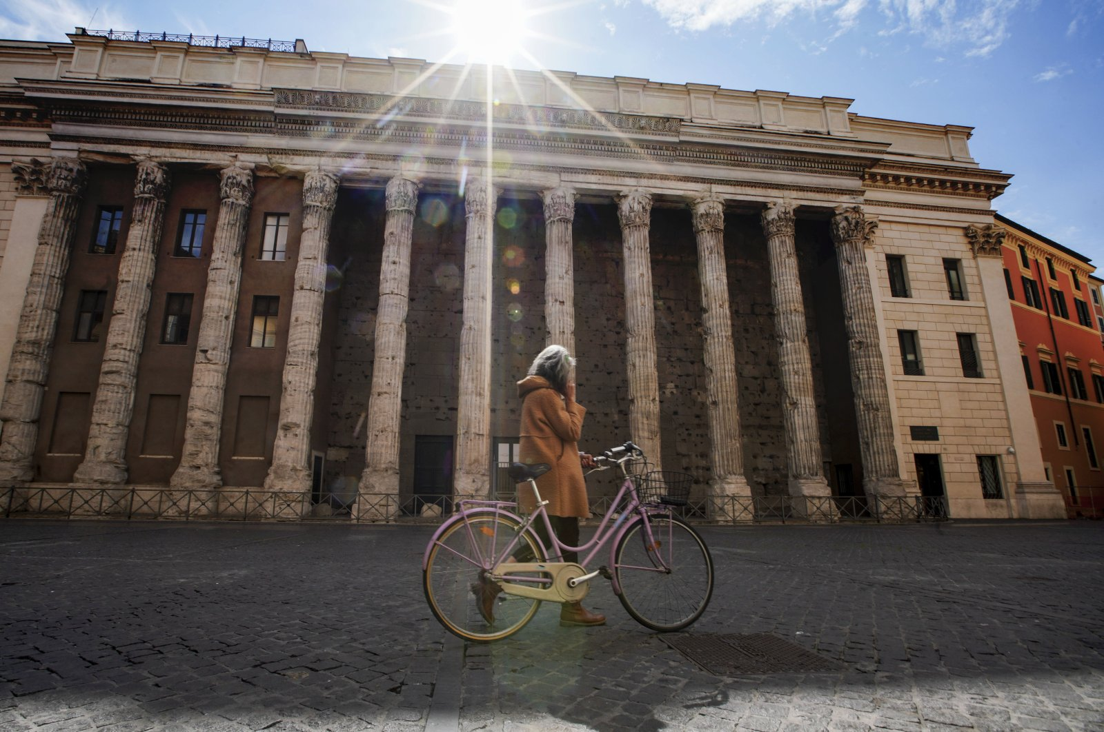 A woman walks in empty Piazza di Pietra square, Rome, Wednesday, March 18, 2020. (AP Photo)