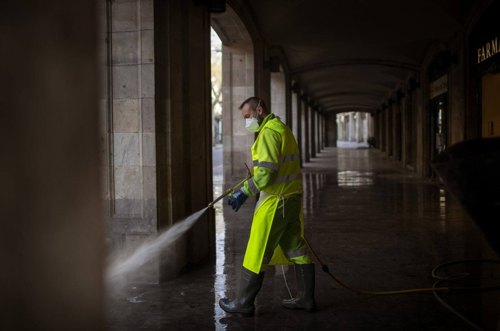 A worker disinfects the street to prevent the spread of the coronavirus in Barcelona, Spain, Thursday, March 19, 2020. (AP Photo)