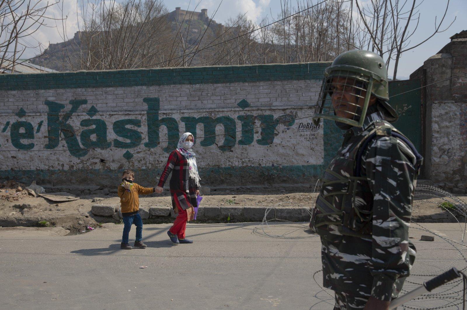 A Kashmiri woman along with her child walks past an Indian paramilitary soldier, Srinagar, Thursday, March 19, 2020. (AP Photo)