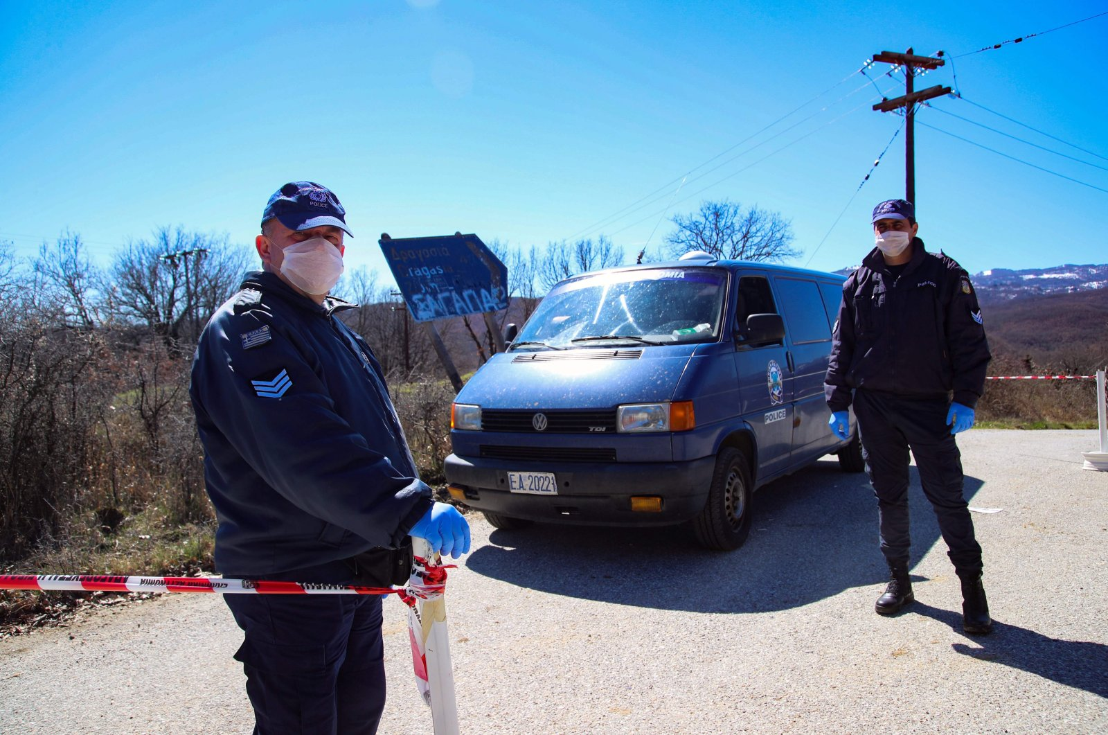 This file photo shows Greek policemen wearing face masks as a protective measure standing guard at a checkpoint on the road to the village of Dragasia near Kozani on Tuesday, March 17, 2020. (AFP Photo)