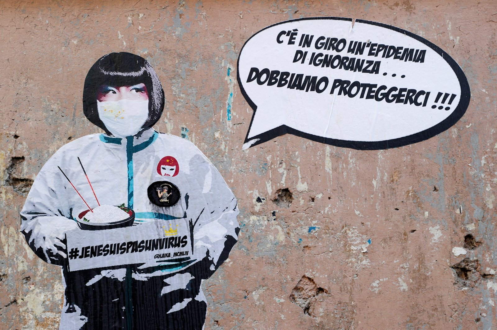 """A mural against xenophobia towards Chinese people is seen after two cases of the coronavirus were confirmed in Italy, by street artist Laika in Rome, Feb. 5, 2020. The mural shows a Chinese woman wearing a protective mask with text reading """"#JeNeSuisPasUnVirus"""" next to words on the wall that read: """"There is an epidemic of ignorance around, we need to protect ourselves."""" REUTERS"""