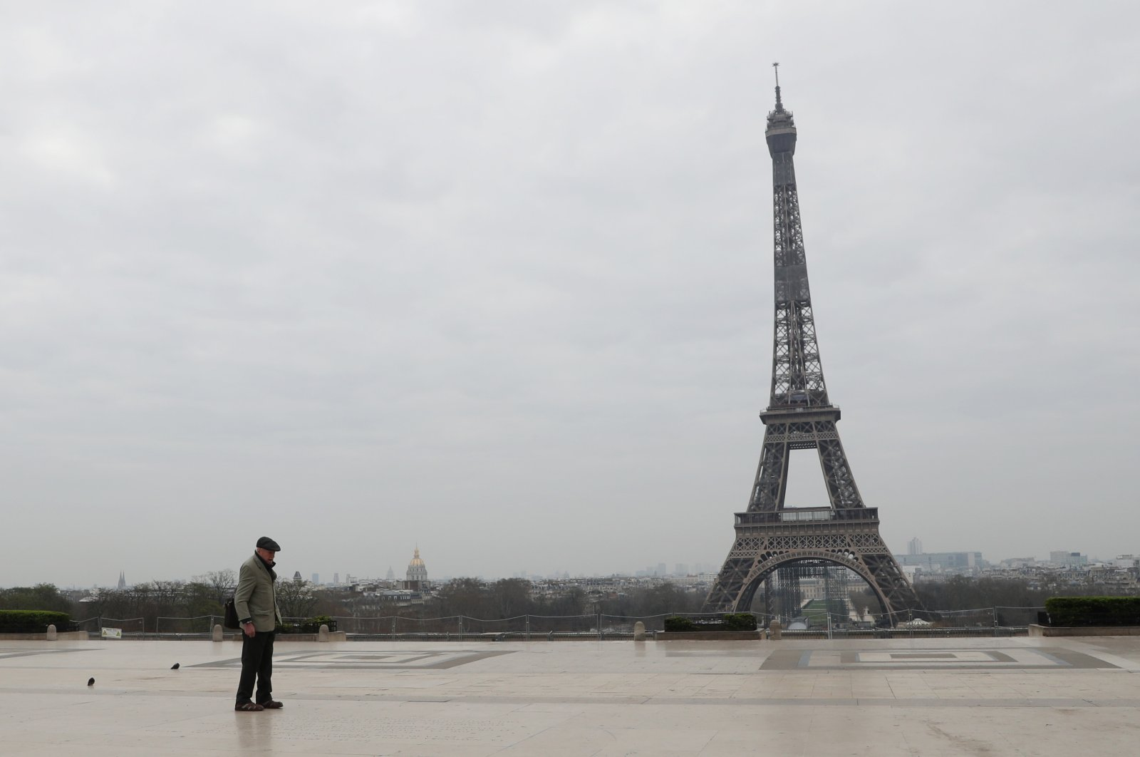 An elderly man walks by the Esplanade du Trocadero square near the Eiffel Tower in Paris, on March 18, 2020 in Paris as a strict lockdown comes into in effect in France to stop the spread of COVID-19, caused by the novel coronavirus. - (Photo by Ludovic Marin / AFP)