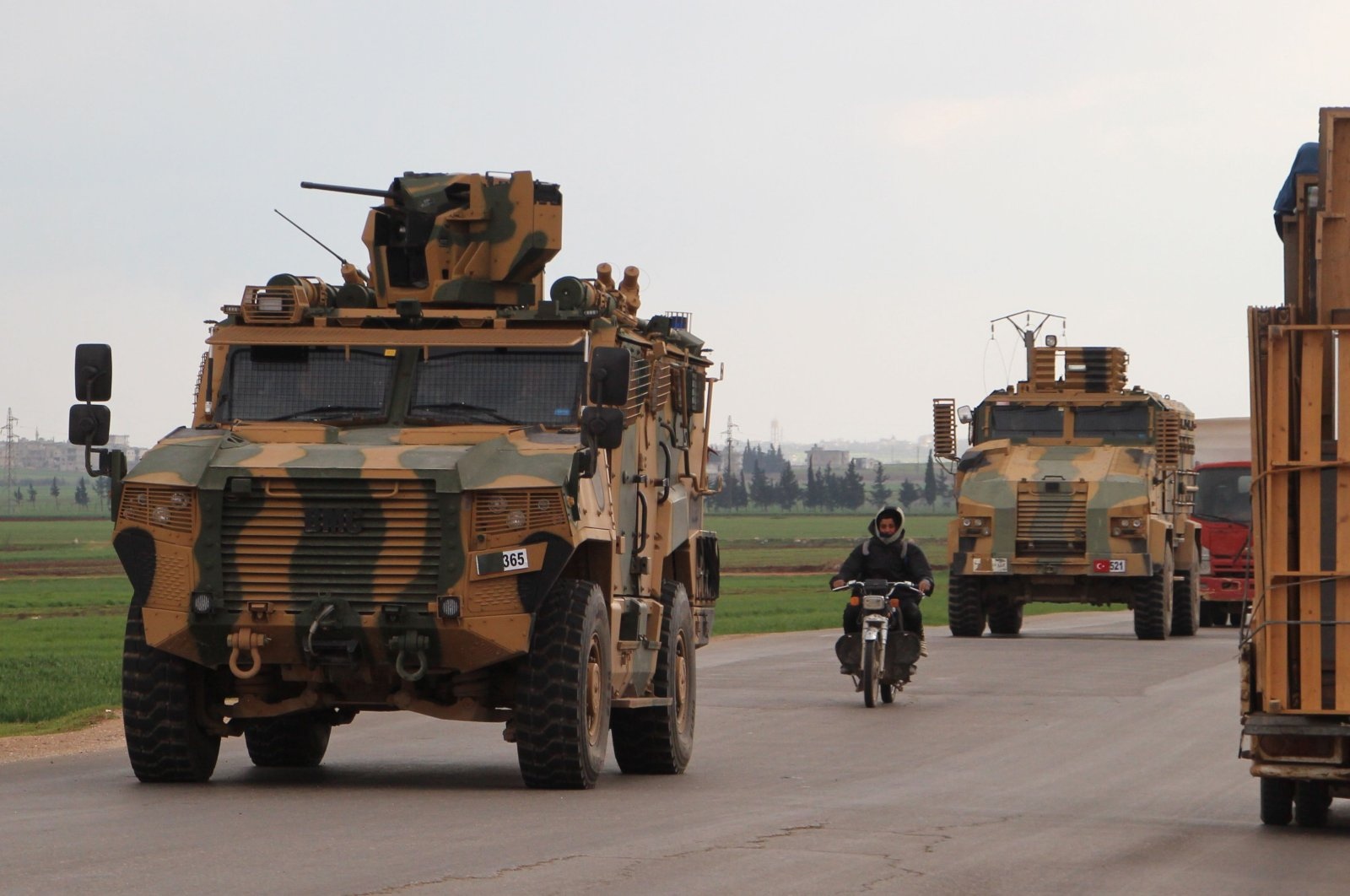 A Turkish military convoy drives on the highway between Bab al-Hawa, crossing on the border with Turkey and the opposition-held town of Ariha, in the northwestern Syrian province of Idlib on March 17, 2020. (AFP Photo)